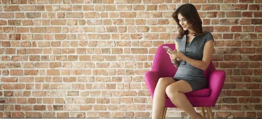 Woman seated in pink chair using mobile phone