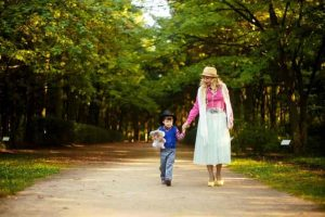 Woman walking hand in hand with boy outdoors