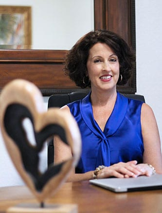 Dana Mayer wearing blue sleeveless blouse seated at her desk.