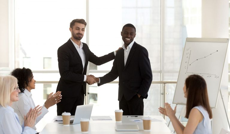 Man gets job promotion and shaking hands with another man