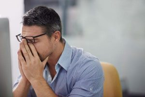 Man with head in hands experiencing job search blues
