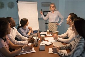 Woman using flip chart in executive leadership training meeting.