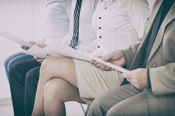 Three executives sitting reading resumes
