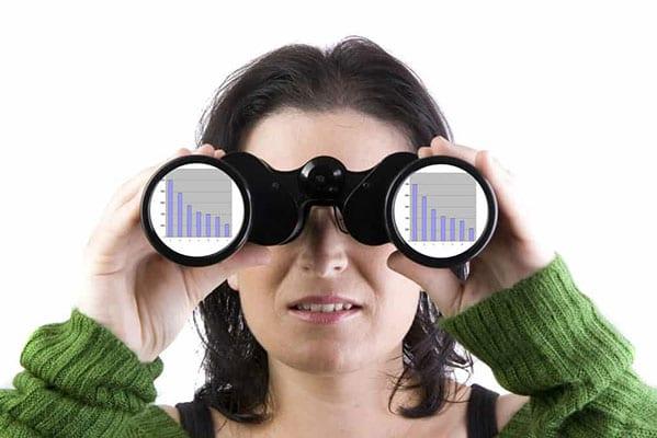 Woman wearing green sweater looking through binoculars
